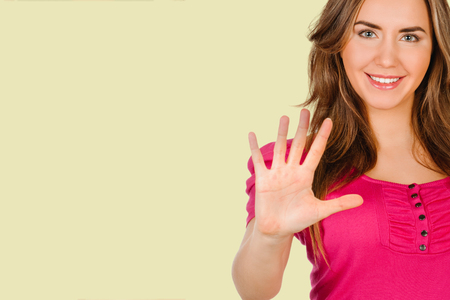 young woman shows sign and symbol on background cream shade YELLOW