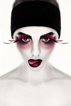 Young creative woman with surrealistic face art showing tongue