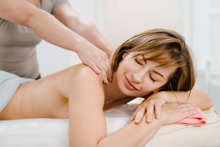 Relaxed young woman enjoying therapeutic body massage Reklamní fotografie