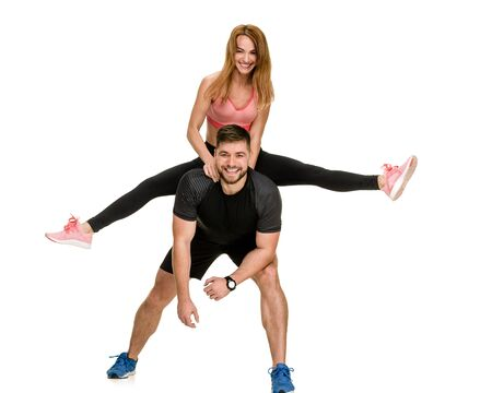 Cheerful sporty people having fun, sportsman piggybacking his girlfriend