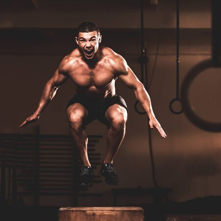 Portrait of muscular sporty man doing box jump exercise