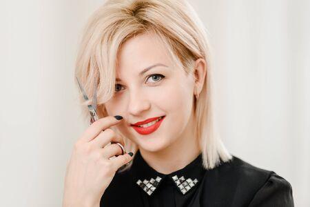 Beautiful blonde female hairdresser holding professional scissors Imagens