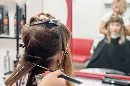 Young professional hairdresser applying dye on clients hair