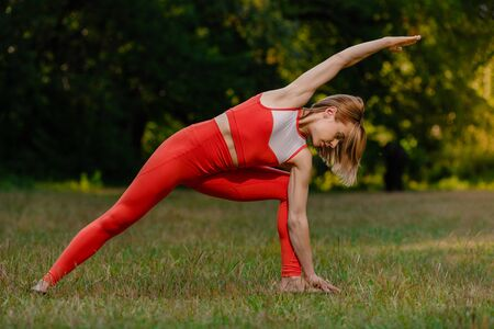 Young healthy woman practicing yoga outdoor in park