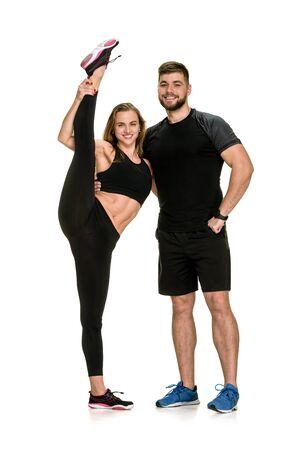 Młody sprawny mężczyzna pomaga elastycznej kobiecie rozciągnąć nogę