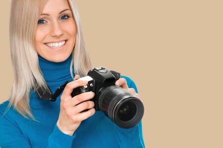 młoda kobieta fotograf z aparatem. na tle brzoskwiniowy odcień żółty