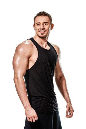 Porträt des jungen lächelnden fitten Bodybuilders, der seinen trainierten Körper zeigt Standard-Bild