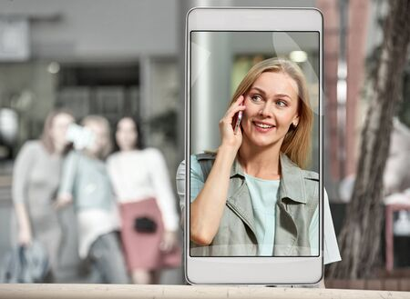 Smartphone displaying photo of young woman talking on phone at mall