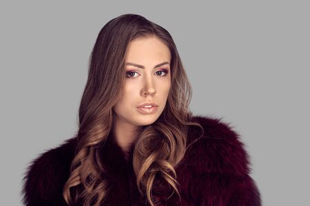 Fashion portrait of attractive brunette woman wearing fur coat