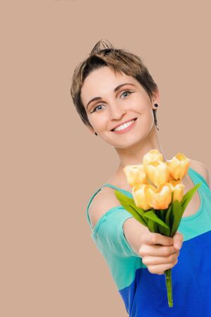 beautiful smiling woman with bouquet of flowers isolated on background salmon shade red Stock Photo