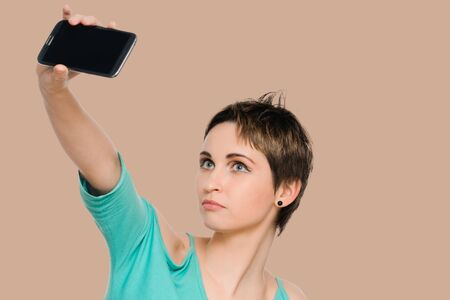 Smiling woman taking a selfie using her smartphone. isolated on background salmon shade red