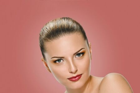 Beauty Girl. Portrait of Beautiful Young Woman looking at Camera. Isolated on on background salmon shade red. Fresh Clean Skin