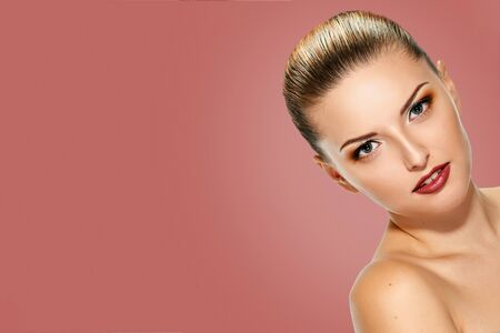 Beautiful face of young adult woman with clean fresh skin on background salmon shade red Stock Photo
