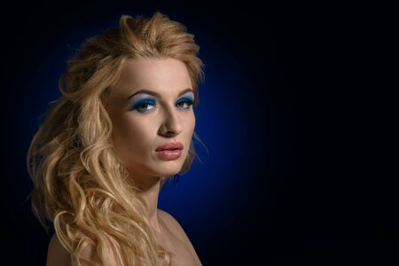 Beautiful blonde woman with long wavy hair on dark blue background with spot Banco de Imagens - 130058447