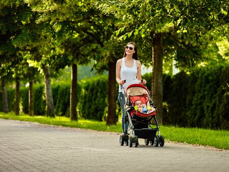 Happy mother walking with babby stroller in summer park 版權商用圖片