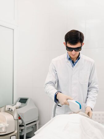 Male doctor cosmetologist in protective glasses doing laser treatment Фото со стока