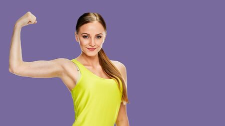 Cheerfully smiling woman doing exercise , isolated on background royal shade violet