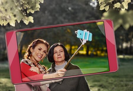 Smiling cheerful family making selfie with monopod in park, smart device concept Фото со стока