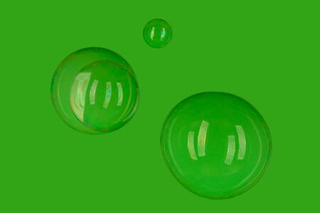 Set of transparent flying soap bubbles on green background 写真素材
