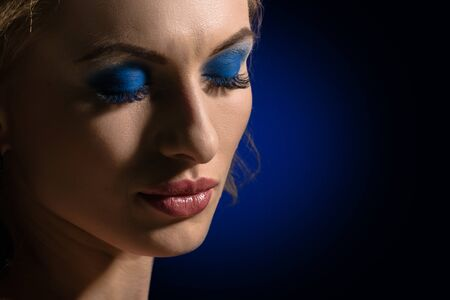 Side view portrait of sensual female model on dark blue background with spot