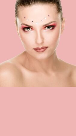 Young pretty woman with creative make-up on pink background, aspect ratio and vertical position convenient for placement on a smartphone