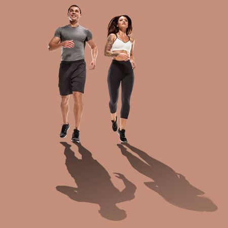 Strong active couple running on brown background with shadow Stock fotó