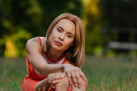 Young attractive woman sitting on grass and stretching muscles on foot