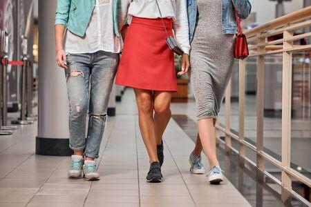 Closeup photo of three modern stylish women walking in the store 写真素材 - 128753836