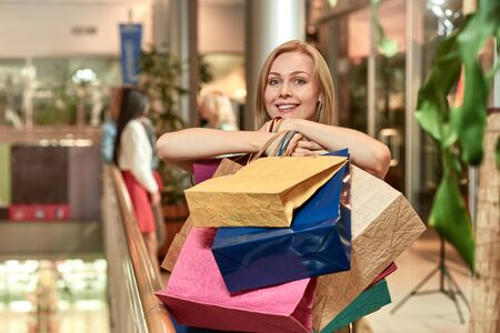 Happy smiling woman with colorful bags and her friends doing shopping 写真素材 - 128753835