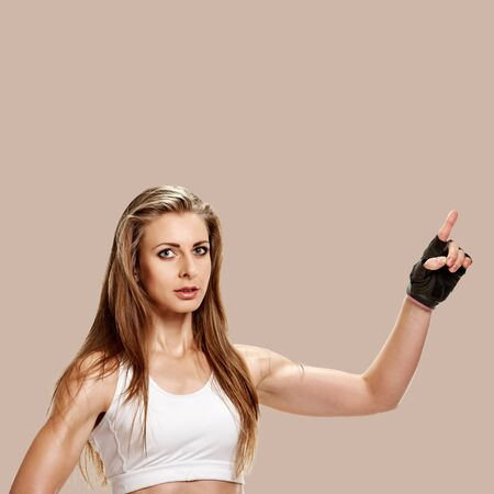 Attractive young sportswoman gesturing on brown background Banque d'images - 128753738