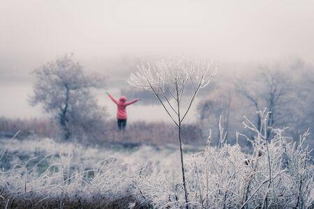 Happy woman enjoying walk on foggy autumn day