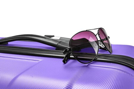 Closeup photo of glasses lying on top of purple valise