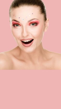 Art portrait of beautiful woman with opened mouth and rhinestones on her face, pink background. aspect ratio and vertical position convenient for placement on a smartphone