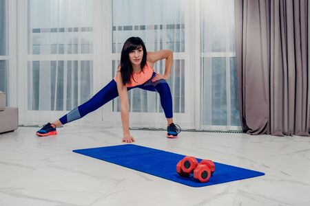 Beautiful young sportswoman doing pilates exercise with dumbbells Banco de Imagens