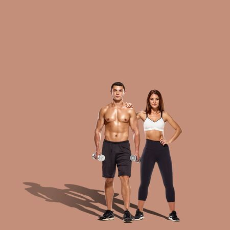 Healthy couple with dumbbells on brown background with shadow on floor