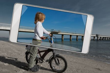 Cute boy with bike on the bulgarian beach, saturated image in smartphone s camera