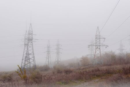 Electricity pillar and power lines on beautiful foggy day Stock fotó