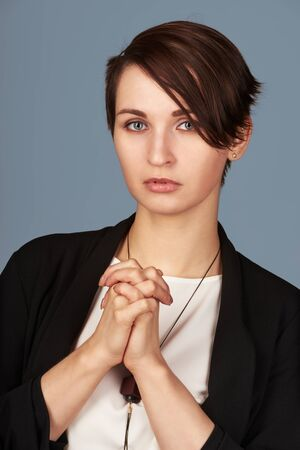 Portrait of young businesswoman making wish and praying for luck Stock Photo
