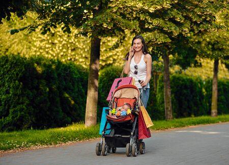 Jeune femme avec une poussette de bébé appréciant parler au téléphone