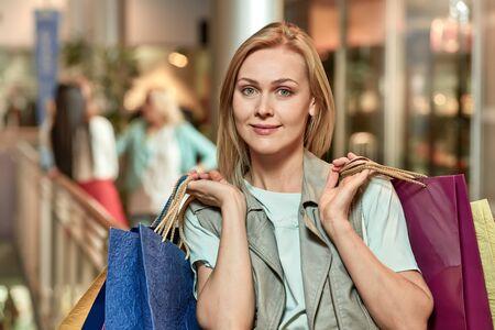 Glücklich lächelnde Frau mit bunten Taschen und ihren Freunden beim Einkaufen Standard-Bild
