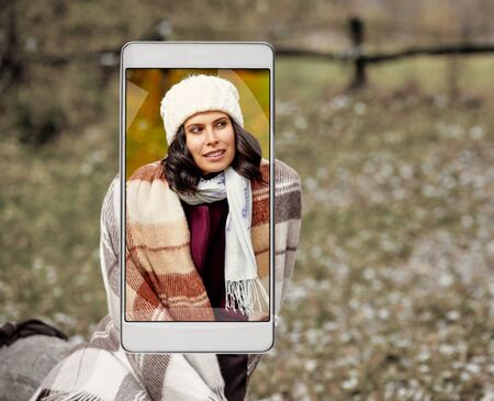 Smartphone displaying photo of stylish woman in autumn forest Stockfoto