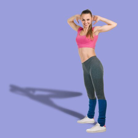Full photo of slim athletic woman doing fitness exercise on violet background Banco de Imagens