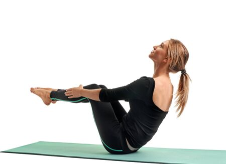 Young woman in black sportswear practicing yoga on mat