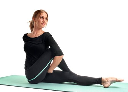 Attractive fit woman doing pilates exercises on yoga mat