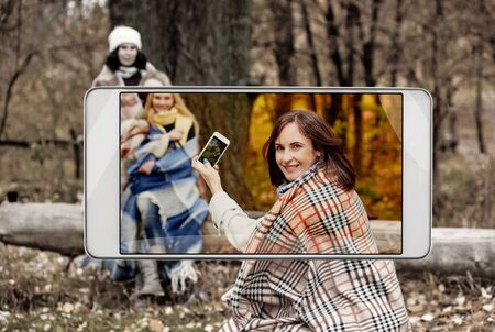 Young woman making photo of her friends in park, smart device concept