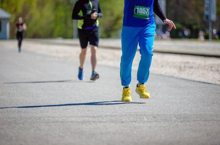 Closeup photo of amateur athletes running during marathon Stockfoto