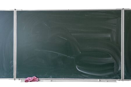 Empty green chalkboard with traces of chalk in school classroom isolated
