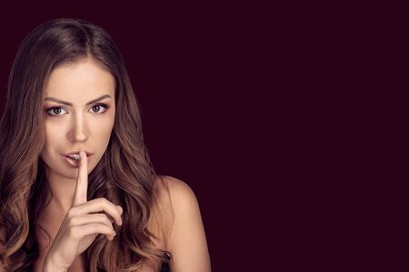 Attractive woman putting her finger to her lips for silence on dark red color background