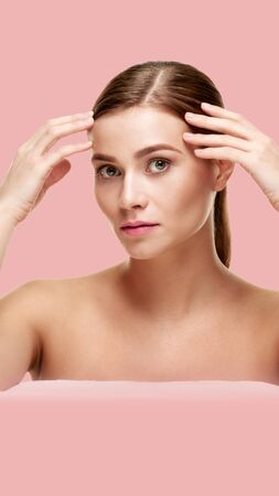 Young woman touching her perfect skin on pink background. Aspect ratio and vertical position convenient for placement on a smartphone