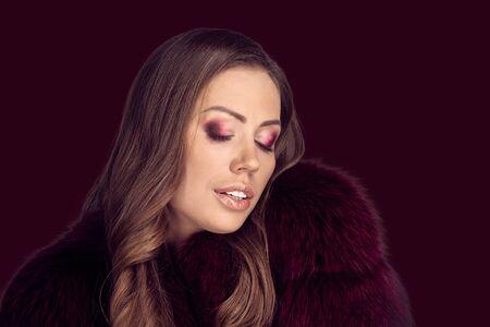 Fashion portrait of beautiful elegant woman in luxury fur coat on dark red color background